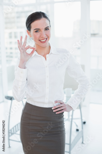 Elegant businesswoman gesturing ok sign in office