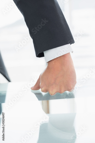 Well dressed businessman with clenched fist on office desk