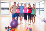 Full length portrait of fitness class at exercise room
