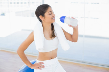 Woman drinking water while sitting on exercise ball