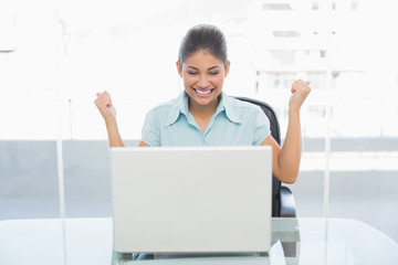 Happy businesswoman clenching fists in front of laptop