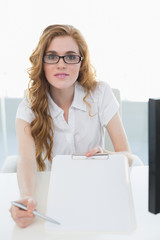 Businesswoman with clipboard at office desk