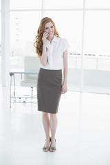 Elegant businesswoman using mobile phone in office