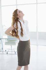 Elegant businesswoman suffering from back ache in office