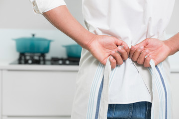 Mid section of man wearing apron in the kitchen