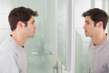 Tensed man looking at self in bathroom mirror