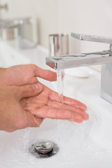 Washing hands under running water at bathroom sink