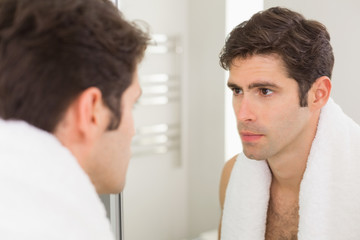 Serious young man looking at self in bathroom mirror