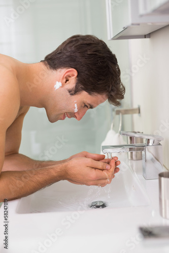 Side view of a man washing face in bathroom