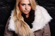 Beautiful blond woman in a fur near bricks wall. winter fashion