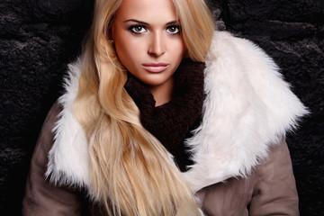 Beautiful blond woman in a fur near bricks wall. winter fashion