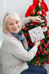 Senior Woman Holding Present By Christmas Tree