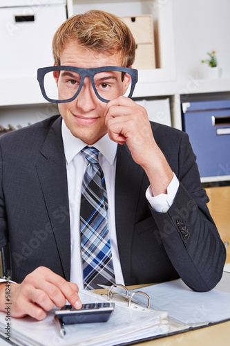 Business man holding nerd glasses in office