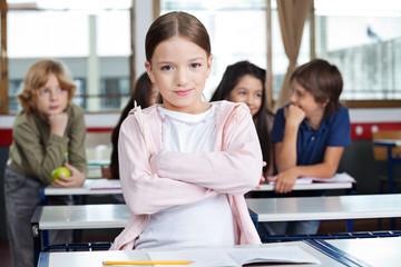 Schoolgirl Standing Arms Crossed In Classroom