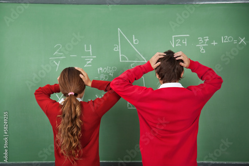 Confused Schoolchildren Standing Against Board