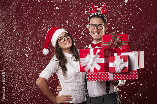 Smiling nerd couple with a lot of christmas presents