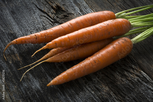 Raw Organic Carrots with Greens on Wood