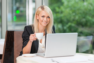 Smiling Blond business lady looking at camera.