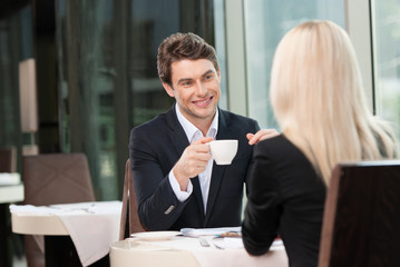 Smiling businessman drinking coffee.