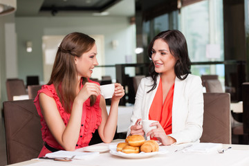 Two girlfriends meet at café for breakfast.