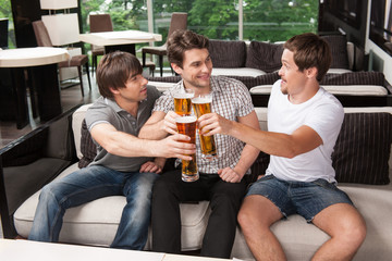 Three male friends drinking cold beer in hot weather.