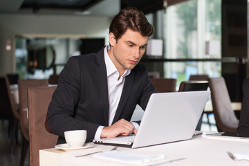 Handsome businessman working with laptop.