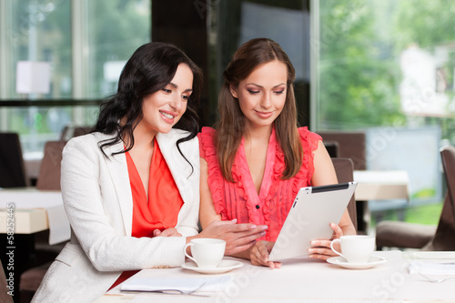 Two female friends looking at ipad.