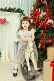 elegant girl sits on horse rocking chair near Christmas fir-tree
