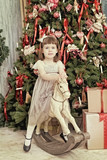 elegant girl sits on a toy horse near a Christmas fir-tree