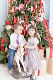 boy and the girl play near a Christmas fir-tree