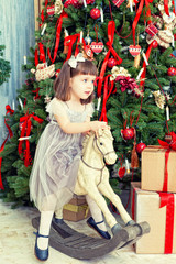 girl shakes on horse rocking chair near Christmas fir-tree
