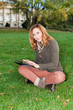 Portrait of beautiful adult woman with tablet pc, outdoors