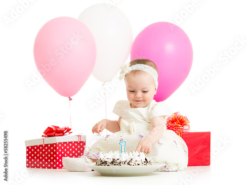baby girl touching birthday cake
