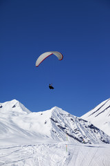 Paraglider in sunny snowy mountains