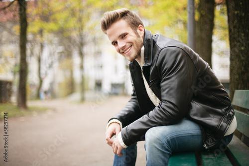 lächelnder Mann auf Parkbank