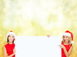 women in santa helper hats with blank white board