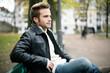junger Mann sitzt auf einer Parkbank