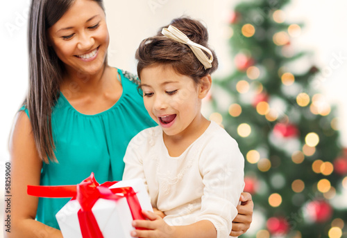 happy mother and child girl with gift box