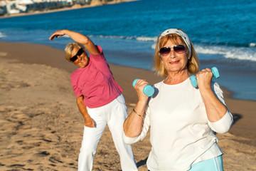 Senior female fitness session on beach.