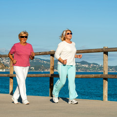 Senior women jogging together outdoors.