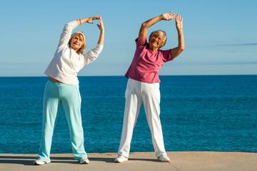 Senior women stretching at seafront.
