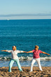 Two female golden agers doing yoga on beach.