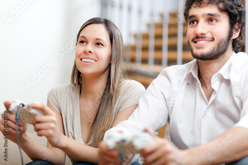 Young couple playing video games in their apartment