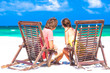 Couple on a tropical beach sitting in chairs