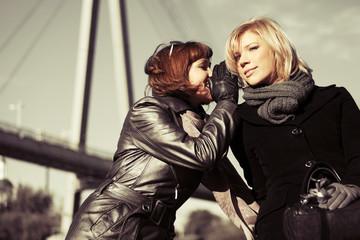 Two young women teeling secrets