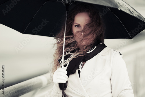 Sad woman with umbrella in the rain