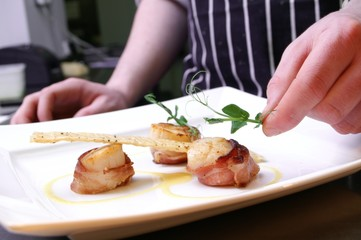 chef plating up plated scallops