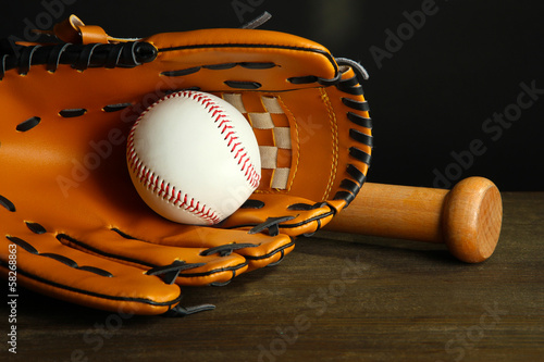 Baseball glove, bat and ball on dark background