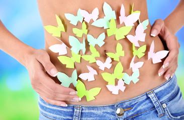 Butterfly on stomach on light background