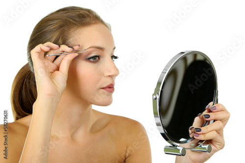 Young woman plucking eyebrows isolated on white